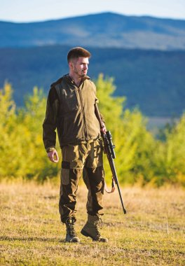 Mental preparation for hunting individual process. Man rifle for hunt. Hunter khaki clothes ready to hunt hold gun mountains background. Hunter with rifle looking for animal. Hunting shooting trophy