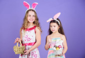 Some bunny loves you. Small girls in bunny headband for Easter celebration. Little girls wearing Easter bunny ears. Cute Easter bunnies bringing eggs. Easter egg is symbol of new lif