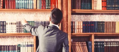 Man takes book from bookcase. Student stands in library and choose book. Guy in smart suit reads near bookcase. Study, learn, education, research, history, literature, wisdom concept. Big library