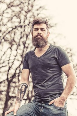 Tired middle-aged man with long beard standing in park on warm spring day. Muscular brutal man with tattooed arm wearing dark blue T-shirt and denim jeans walking in urban scene