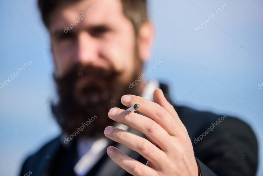 Cigarettes help us with everything from boredom to anger management. Bearded hipster smoking cigarette sky background. Guy cigarette enjoy nicotine influence. Man with beard mustache hold cigarette