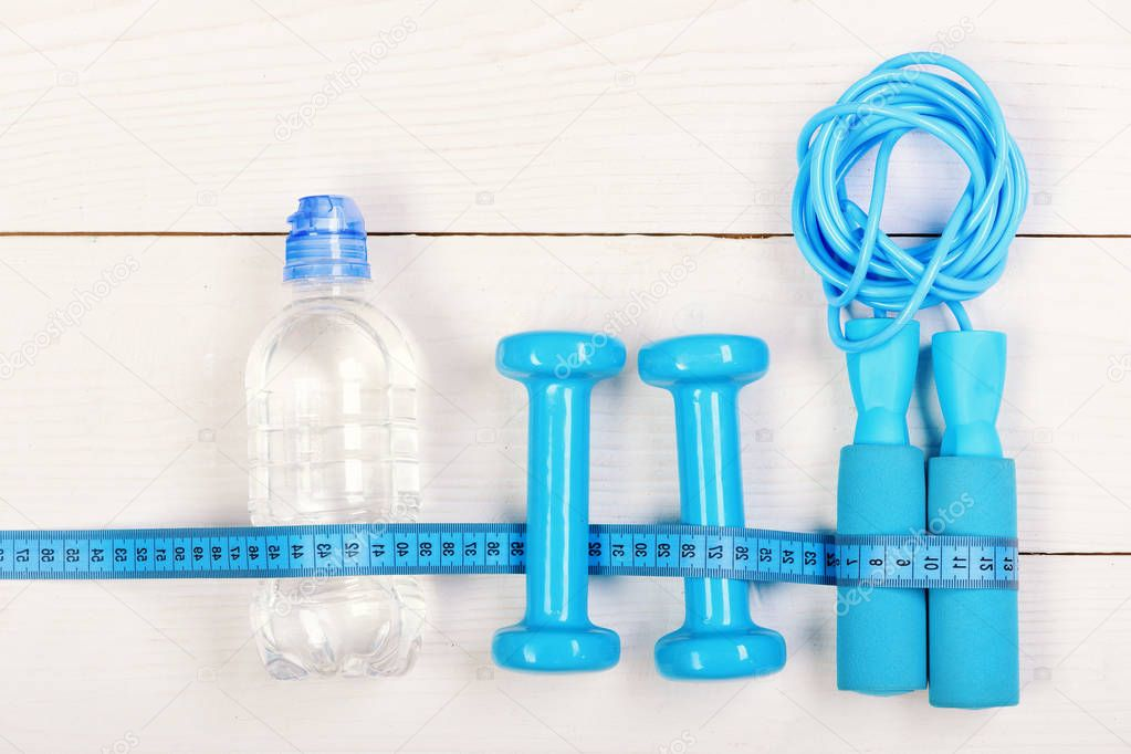 Active lifestyle and shaping concept. Centimeter tied around gym tools