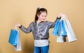Fotografie Einzelhandel. Urlaubskauf sparen. Fröhliches Kind. Kleines Mädchen mit Geschenk. Verkaufsrabatte. Mode und Stil. Kunde mit Packung. Kleines Mädchen mit Einkaufstaschen. Unbedingt. Muss sein. Es ist ein Muss