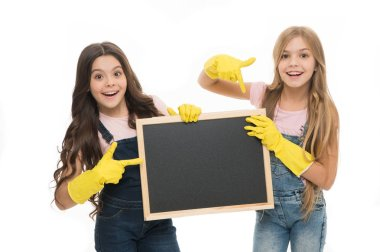 A little help for keeping things tidy. Adorable tidy schoolgirls in rubber gloves pointing at tidy blackboard. Primary school children keeping their school supplies clean and tidy, copy space
