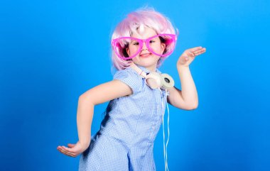 The coolest modern music. Little modern girl in party style wearing bluetooth headphones. Small child enjoy dancing to modern music every day. Using modern technology for pleasure