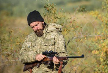Man aiming target nature background. Hunter hold rifle. Aiming skills. Hunting permit. Bearded hunter spend leisure hunting. Hunting equipment for professionals. Hunting is brutal masculine hobby