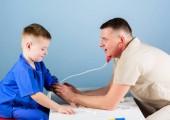 Pečlivý pediatr zkontrolujte zdraví dítěte. Lékařské vyšetření. Nemocniční pracovník. Lékařská služba. Doktor se posadil na stolní lékaře a prohlížel si pacienta s malým chlapcem. Zdravotní péče. Koncepce pediatrii