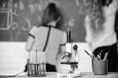 Pupil at chalkboard on chemistry lesson. Educational experiment concept. Girls classmates study chemistry. Microscope and test tubes on table. Chemical reactions. Make studying chemistry interesting. stock vector