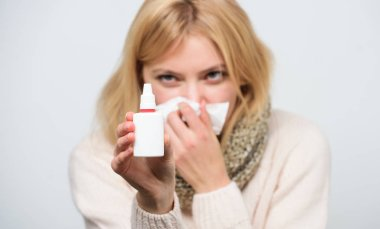 Relieving itchy nose. Cute woman nursing nasal cold or allergy. Sick woman spraying medication into nose. Treating common cold or allergic rhinitis. Unhealthy girl with runny nose using nasal spray
