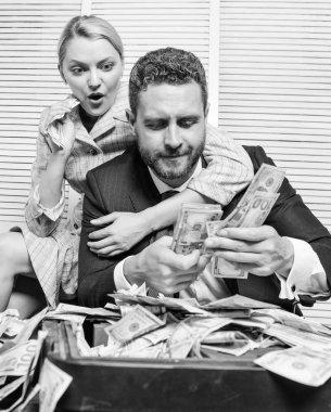 Businessman near cash dollars profit. Huge profit concept. Financial success. Counting money profit. Man businessman and woman secretary with pile dollar banknotes. Profit and richness concept
