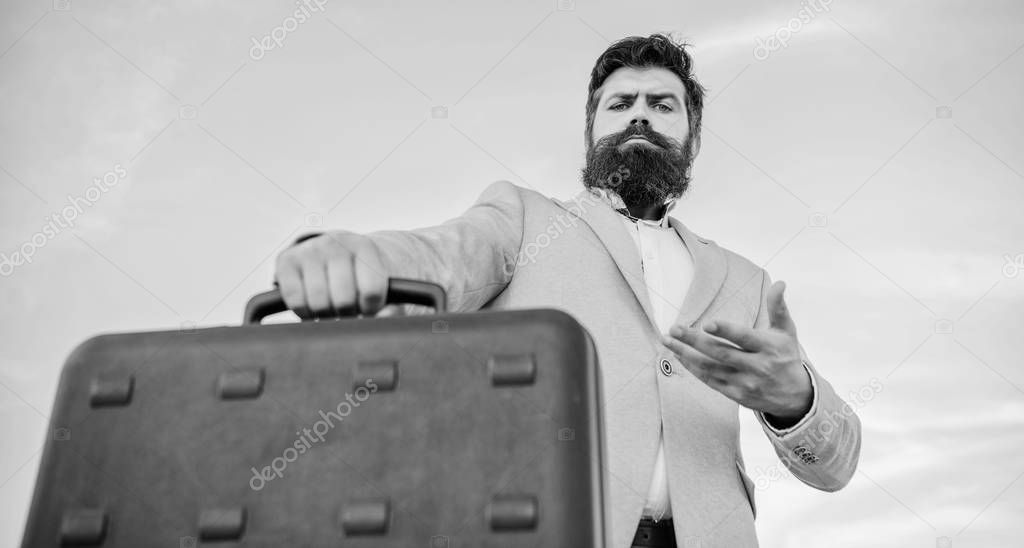 Hipster bearded face hold briefcase with bribe. Business man formal suit carries briefcase sky background. Businessman presenting business case. Entrepreneur offer bribe. Illegal deal business