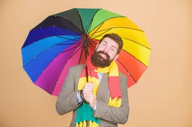 Prepared for rainy day. Carefree and positive. Enjoy rainy day. Predict future weather trends. Man bearded guy hold colorful umbrella. It seems to be raining. Rainy days can be tough to get through