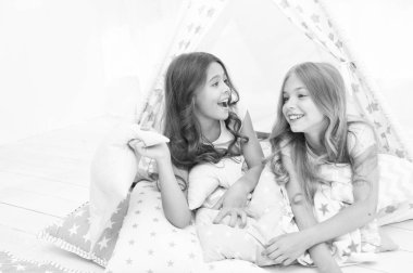 Sisters friends share gossips having fun at home. Pajamas party for kids. Siblings best friends. Sisters or best friends spend time together in bedroom. Girls having fun together. Girlish leisure