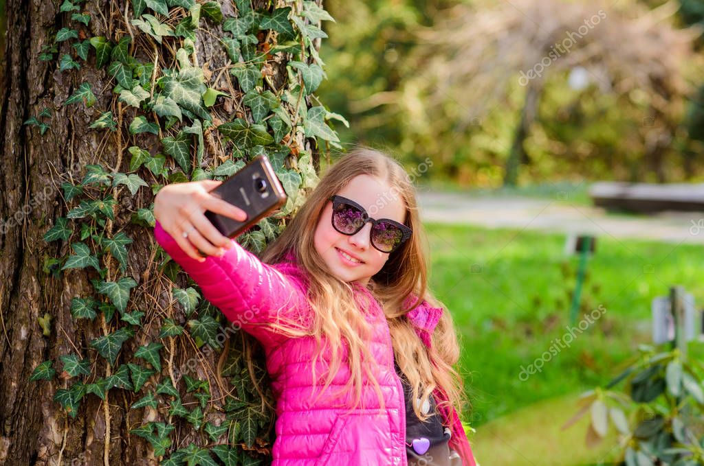 Enjoying nature in garden. Peaceful environment garden. Kid cute fancy child spend time in park. Plants grown for display to public. Pleasant relaxing walk in garden. Girl walk in botanical garden