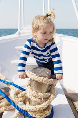 dreamer kid in striped marine shirt. small sailor on boat. let dream come true. summer vacation. child dream to be sailor. traveling. happy small boy on yacht. boat trip by sea. this is my dream