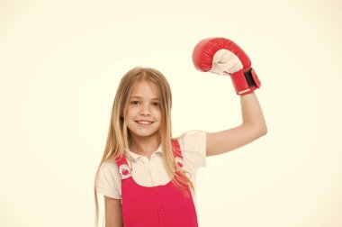 Girl on smiling face posing with boxing glove, isolated on white background. Kid girl with long hair knows how to defend herself. Girls power concept. Girl likes boxing and sporty lifestyle