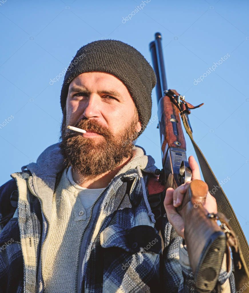 Hunter with rifle gun close up. Guy bearded hunter spend leisure hunting and smoking. Hunting masculine hobby concept. Man brutal bearded guy gamekeeper blue sky background. Brutality and masculinity