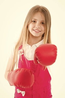 Girls power concept. Girl on smiling face posing with boxing gloves, isolated on white background. Girl likes boxing and sporty lifestyle. Kid girl with long hair knows how to defend herself