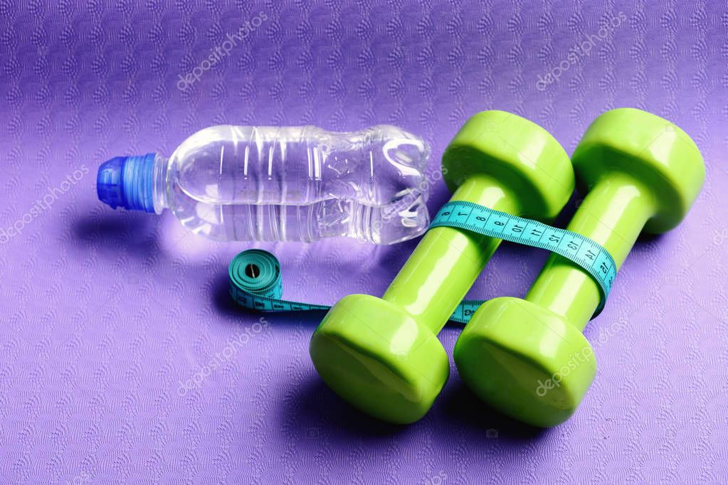 Healthy shape and sport concept. Barbells next to tape measure