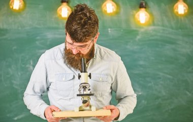 Man with beard and mustache on busy face. Scientist holds book and microscope, chalkboard on background. Scientific research concept. Teacher in eyeglasses holds book and microscope