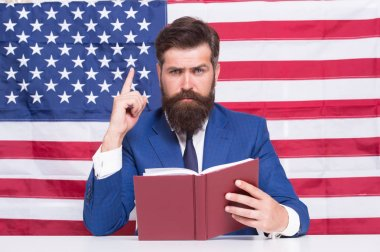 Patriotic concept. American lawyer teacher or tv host hold book american flag background. Love homeland. Man with beard and mustache serious face with american flag. Make America great again