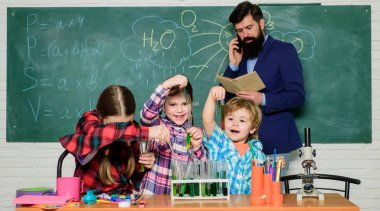 doing experiments with liquids in chemistry lab. chemistry lab. happy children teacher. back to school. kids in lab coat learning chemistry in school laboratory. Professional choice