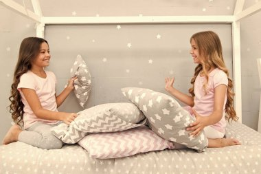 Sisters communication. Children relax and having fun in evening. Sisters leisure. Girls in cute pajamas spend time together in bedroom. Sisters communicate while relax in bedroom. Family time