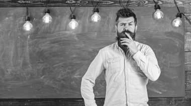 Intellectual task concept. Man with beard and mustache on thoughtful face stand in front of chalkboard. Bearded hipster in shirt, chalkboard on background. Guy thinking with thoughtful expressio