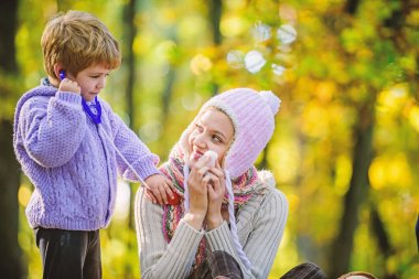 Happy son play with mother like doctor. relax in autumn forest. Spring mood. seasonal cold. Happy family day. Mother love her small boy child. cold weather. Healthy life. Family outdoor. Mothers day