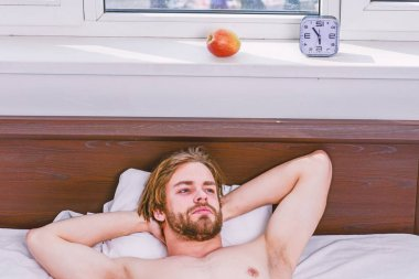 Lazy man happy waking up in the bed rising hands in the morning with fresh feeling relaxed. Morning of a new day, alarm clock waking up man stretch the muscles, health concept.