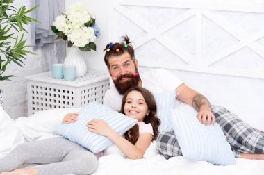 Father bearded man with funny hairstyle ponytails and daughter in pajamas. Dad and girl relaxing in bedroom. Pajamas style. Having fun pajamas party. Slumber party. Happy fatherhood. Close friends