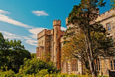 Victorian style architecture and design. Lews Castle in garden of Stornoway, United Kingdom. Castle with green trees on blue sky. Landmark and attraction. Summer vacation and wanderlust