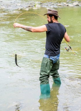 Fishing masculine hobby. Brutal man wear rubber boots stand in river water. Fisher weekend activity. Fisher with fishing equipment. Fish on hook. Leisure in wild nature. Fun of fishing is catching