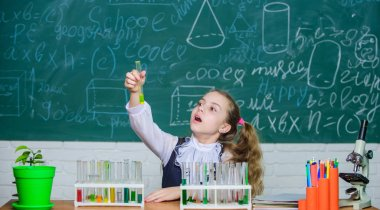 Interesting approach to learn. Girl cute school pupil play with test tubes and colorful liquids. School chemical experiment. School education. Future scientist. Explore and investigate. School lesson