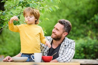 Food habits. Little boy with dad eating food picnic yard nature background. Summer breakfast. Healthy food concept. Family weekend. Father son eat food and have fun. Menu for children. Homemade meal