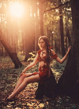 Sexy dreaming. cougar female. ethnic tribal fashion. deep forest. wild woman in forest. amazon woman. sexy witch. sexy girl in leather suede clothes. female silhouette through the sun rays