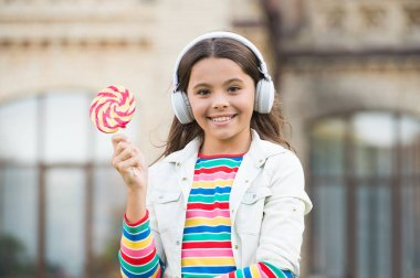 Happy kid singing sweet candy mic. Happy childhood. Kid child headphones holding lollipop candy. Happy kid with candy outdoors having fun. Calories and energy. Schoolgirl deserve dessert. Sweet remix