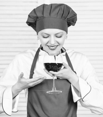 somellier with wine glass. woman in cook hat and apron. professional chef in kitchen. Cuisine. Housewife drink red wine. happy woman. Cheers to friends. Sommelier examining wine. This is perfect wine