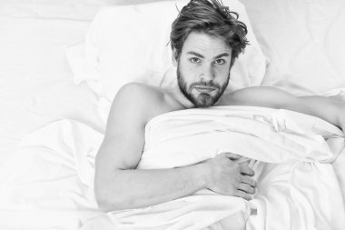 Picture showing young man stretching in bed. Man eyes are closed with relaxation. Morning bed active funny.