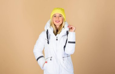 design is perfect. woman in padded warm coat. happy winter holidays. New year. beauty in winter clothing. cold season shopping. flu and cold. seasonal fashion. girl in beanie hat. faux fur fashion