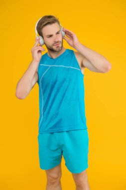 Everyone needs a tune-up. Sportsman listen to music. Sportsman training to tune. Strong sportsman wear headphones and fitness uniform. Healthy sportsman or athlete. Sport and fitness. Regular workout