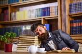 přepracovaný muž spí na otevřené knize s mnoha dalšími na stole