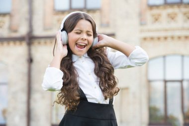 child has music break. girl in headphones. pretty little girl wear classy uniform. back to school. modern education with new technology. kid sing at schoolyard. dream to be a singer