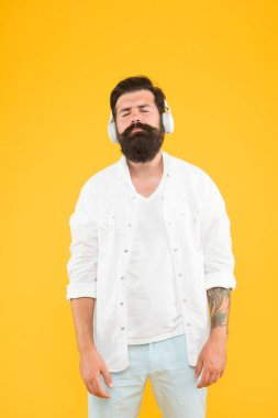 Audio enjoyment. Perfect sound. Hipster listen music stereo headphones. Modern wireless headphones. Electronic music and house tracks. Instrumental music. Bearded man headphones yellow background