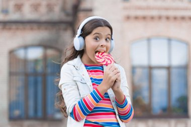 Sweet dreams. healthy food. child has music break. girl in headphones. little girl in wireless headset with lollipop. back to school. modern education with new technology. kid at schoolyard
