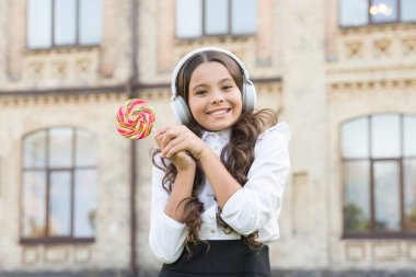 sweet makes her happy. modern look of schoolgirl. kid in headset hold lollipop. pupil listen music. back to school. beauty with candy. kid innovating education. happy childrens day. my sweet life