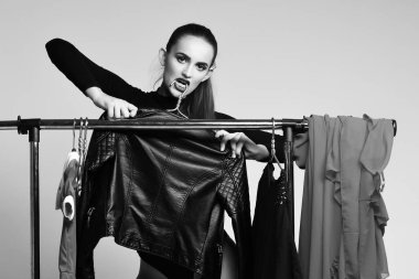 Pretty girl posing with clothing and black jacket on hangers