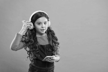 choosing favorite song. e-learning in modern life. schoolgirl use new technology. copy space. kid listen music in headphones. small child make play list on smartphone. small girl hold mp3 player