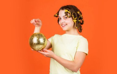 Fashion girl posing in curlers on orange background. saturday night and disco ball. baby shower party. lets have fun on retro party. disco ball decoration. lovely girl with disco ball