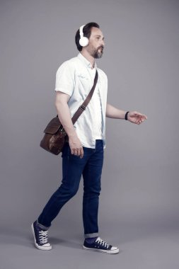 Dont stop music. Bearded man listen to music on foot. Mature person wear headphones playing music. Casual fashion style. New technology. Modern life. Music lifestyle, vintage filter